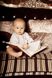 Small child in the interior reading a book. Smiling baby in the Royalty Free Stock Images