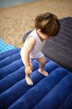 The small child jumps on an inflatable mattress Royalty Free Stock Photo