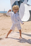 Small child kidding standing on a beach. In a sunny day Stock Image