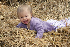 Small Child Laughing in a Pile of Straw Royalty Free Stock Images