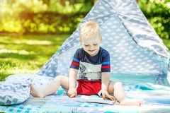 A small child laughs and reads a book in the park. Boy preschool. The concept of childhood, learning and lifestyle Royalty Free Stock Images
