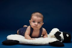 Small child lay on blue pillow. Small child lay on pillow in blue studio background. Kids theme royalty free stock photo