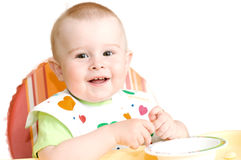 A small child learns to eat on his own Stock Photo