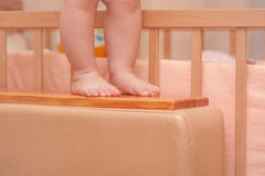 Small child legs near the cot royalty free stock images