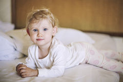 Small child lies in the bedroom on the bed and smiling stock photography