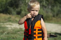 A small child in a life jacket thought. Before walking on the water on the boat royalty free stock photography