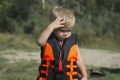 A small child in a life jacket thought. Before walking on the water on the boat stock image