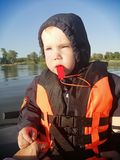 A small child in a life jacket and a whistle. Sitting in a boat that floats on the water stock image