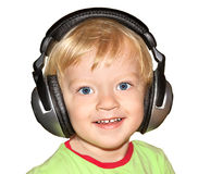 Small child listens to music in the headphones isolated on a whi Royalty Free Stock Images