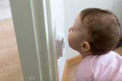 Small child is looking at an electrical outlet at home. Safety of children.  Royalty Free Stock Photo