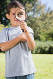 Small child looking through a magnifying glass Royalty Free Stock Photography
