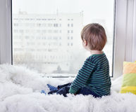 Small child looking out the window Royalty Free Stock Photo