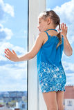 Small child looking through window, standing on window sill Royalty Free Stock Image