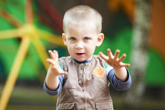 Small child looks into the camera. And holds out his hand to us royalty free stock photo