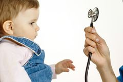 A small child looks at the stethoscope and pulls his hand to it royalty free stock photo