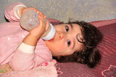 Small child lying and drinking milk product from bottle Royalty Free Stock Images