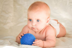 Small child lying on his stomach and holding the ball for massage Stock Photo
