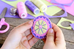 Small child made a beautiful flower from felt circles and beads. Child holds a felt flower in hands. Felt flower DIY Stock Photography