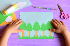 Small child made a Earth day card. Materials and tools for create a simple kids crafts. Children`s hands on a desktop. Earth day paper crafts concept for kids royalty free stock image