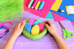 Small child made Easter decoration. Child holds beautiful felt Easter eggs and sisal nest decoration in his hands Royalty Free Stock Photos