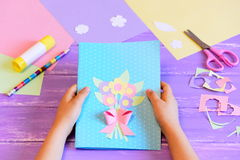 Small child made a greeting card with flowers for mom. Child holds a card in his hands. Step Royalty Free Stock Photos