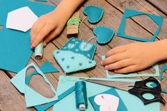 Small child made a house with hearts ornament of felt. Materials and tools for making felt ornaments Royalty Free Stock Photos