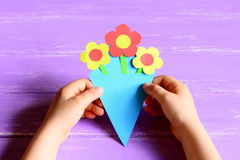 Small child made paper flowers crafts for mother`s day or birthday. Child holds and shows a paper bouquet. Creative activities for preschoolers. Top view. Mother stock photo