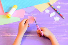 Small child makes a greeting card for mom. Child holds scissors and cuts a flower from paper. Step Royalty Free Stock Photos