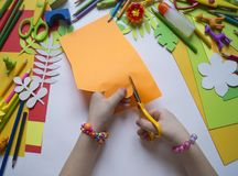 Girl draws. Children`s creativity. Favorite hobby for children. Materials and tools. Small child makes paper crafts for mother`s day or birthday. Small child Royalty Free Stock Photos