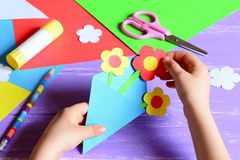 Small child makes paper crafts for mother`s day or birthday. Small child doing paper flowers for mom. Simple and nice gift idea Stock Image