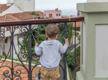 A small child observes something while holding on to railings royalty free stock photos