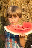 The small child outdoors eats water-melon Royalty Free Stock Photos