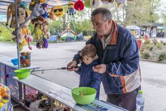 Small child palying fish the ducky. Young boy playing catch the rubber ducky at a outdoor amusement park. His grandfather helping him royalty free stock image