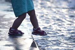Small child on the pavement makes a dangerous step into the water. The a small child on the pavement makes a dangerous step into the water stock photos