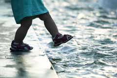 Small child on the pavement makes a dangerous step into the water. The small child on the pavement makes a dangerous step into the water stock image