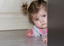 A small child peeks out from behind the wardrobe. The girl with long hair. stock image