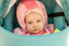 A small child in a pink hood. Little blue-eyed girl sitting in a blue wheelchair in a pink hood. Beautiful blue eyes looking into the camera. The gaze of the Stock Images