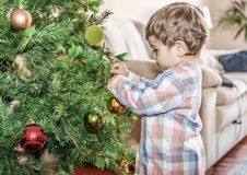 A small child places colorful balls on the Christmas tree in the living room. Of his home stock photography