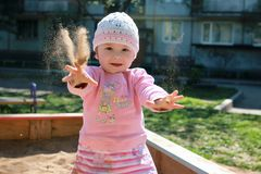 Small child playing in the backyard and in the sandbox Stock Photography