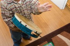 Small child playing on drum Stock Images