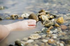 Child playing with her feet and rocks in lake. Small child playing with her feet and rocks in lake muddy water during daytime Stock Photo