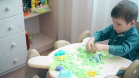 A small child is playing with kinetic sand and develops motor skills of hands stock footage