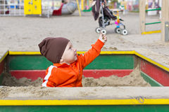 Small child is playing in sandbox. Portrait of a smiling baby boy on kids playground in city in autumn season in Russia Stock Image