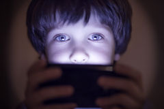 Small child playing on a smartphone stock image