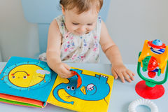 Small child playing with soft book stock image