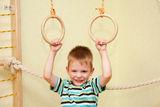 Small child playing sports at sport center. Kid exercising on gymnastic rings royalty free stock images