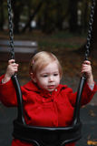 Small child playing on swing in a sunny playground park Royalty Free Stock Photo