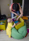 A small child is playing with toys in a box with mom Stock Photo