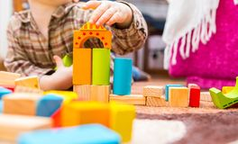 Small child playing with wooden blocks Royalty Free Stock Photo