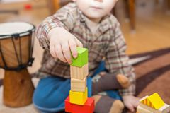 Small child playing with wooden blocks Stock Photo